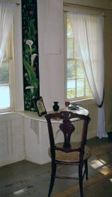 Louisa May Alcott's shelf desk in her bedchamber at Orchard House; calla lilies and other artwork on the wall above the desk painted by her sister, May. Images used by permission of Louisa May Alcott's Orchard House